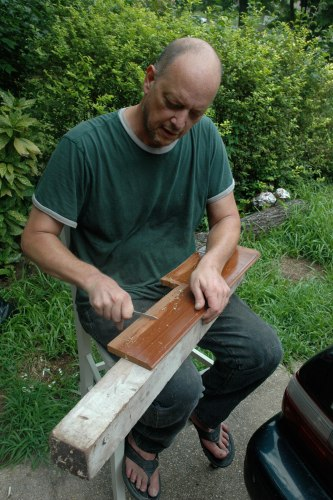 One of the lessons Bill Kinneary teaches his furniture repair and restoration workshop participants is how to use a knife, instead of chemicals, to strip paint from certain pieces of wood. Here demonstrates this skill at his garage workshop in Cheverly, Md.