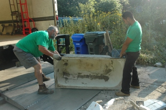 Community Forklift employees Tom Jamison and Ulises Solozano prepare to hoist a bathtub into the nonprofit's box truck after chatting with donor Joy Melnick at her home in a College Park neighborhood.