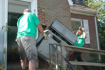 Community Forklift employees Tom Jamison and Ulises Solozano maneuver a donated stove out of Joy Melnick's house in a College Park neighborhood.