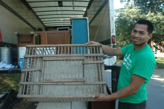 Ulises Solozano shows off the wooden chicken crate that Nancy Traubitz donated to Community Forklift after downsizing her belongings at her house in Silver Spring.