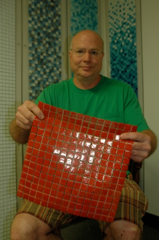 Gary Piscopo hold up a sample of the type of glass mosaic tile that Wholesalers USA Inc. donated to Community Forklift in late September.