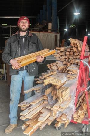 Doug showing off bundles of flooring