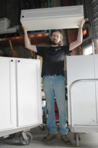 Arranging donated kitchen cabinets, one of the Forklift's top-selling items, is like stacking adult building blocks for Doug Utterback.
